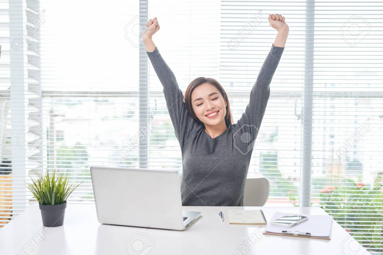 Satisfied woman relaxing with hands behind her head. Happy smiling employee after finish work, reading good news, break at work, girl doing simple exercise, relieve muscle stress, feeling well - 126710524