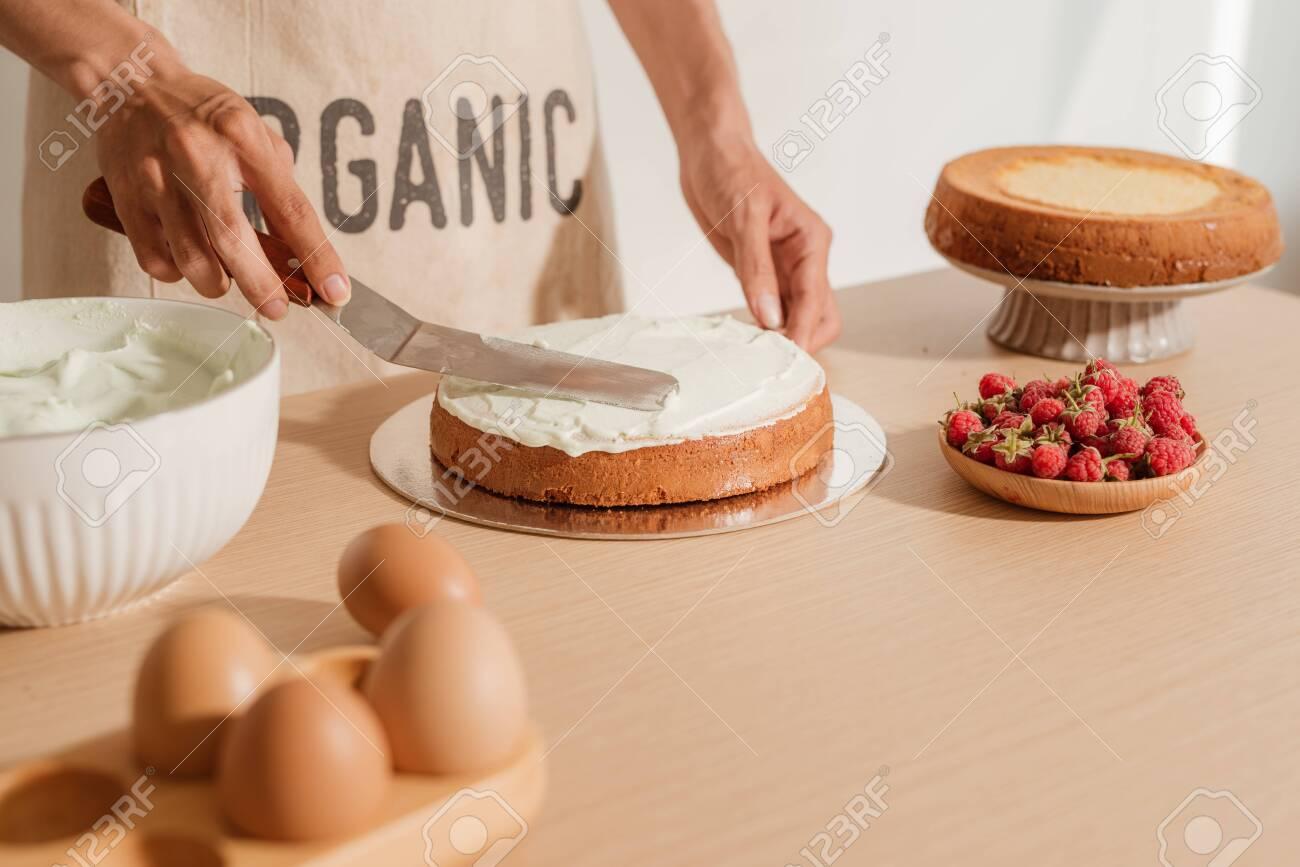 Man putting cream on sponge cake. Making home-made cake process - 127679305