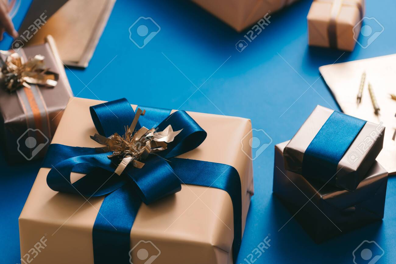 Gold boxed with blue ribbon on blue background. Xmas concept - 129111367