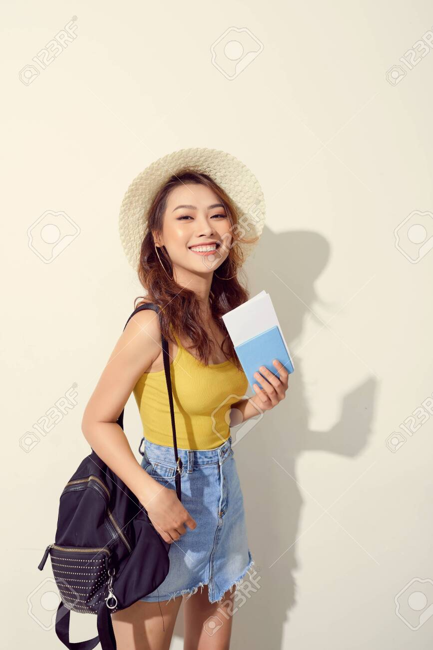 Sunny lifestyle fashion portrait of young woman wearing trendy outfit, straw hat, travel with backpack - 129066963