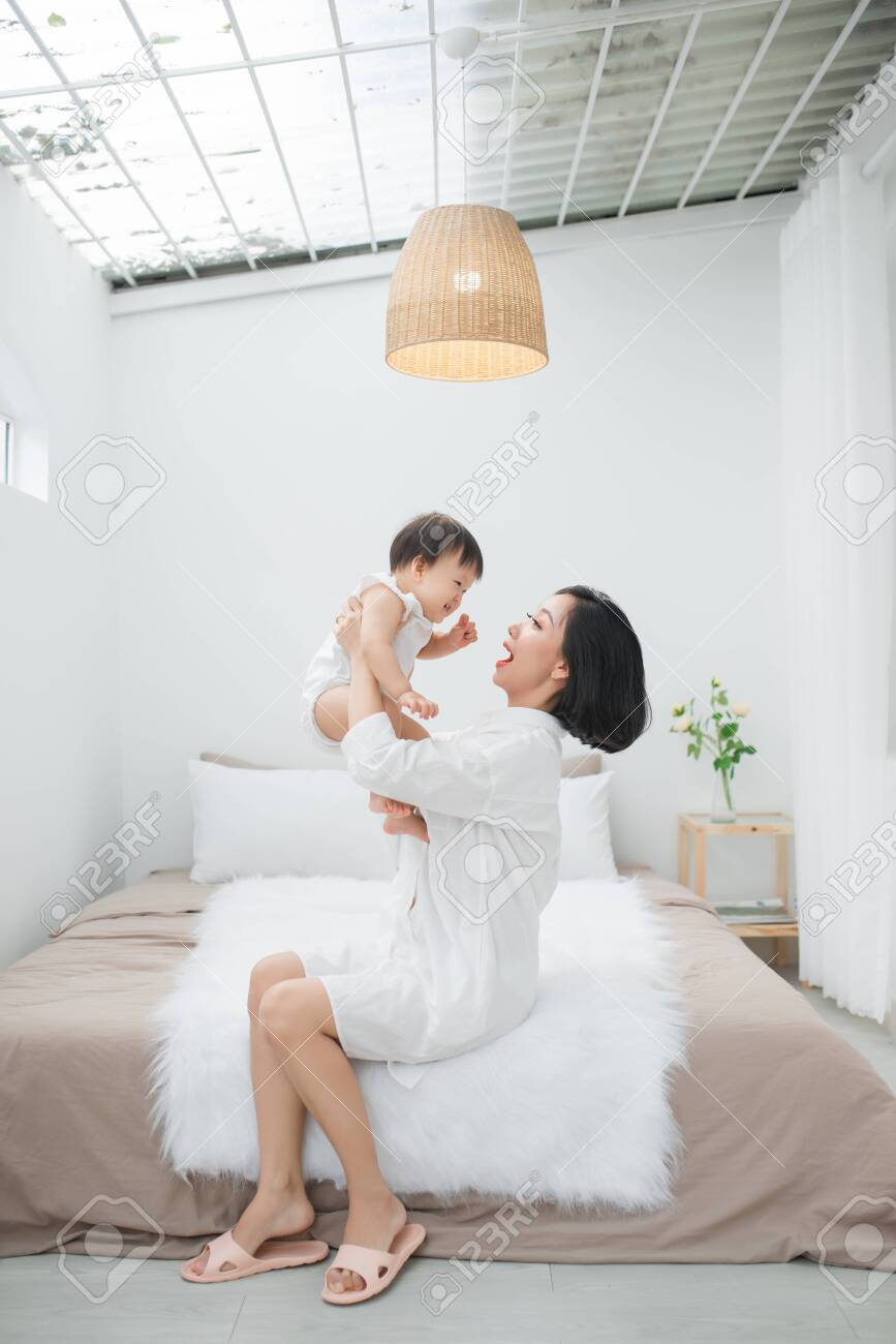 Young mother playing with her little girl at the bedroom - 129068411