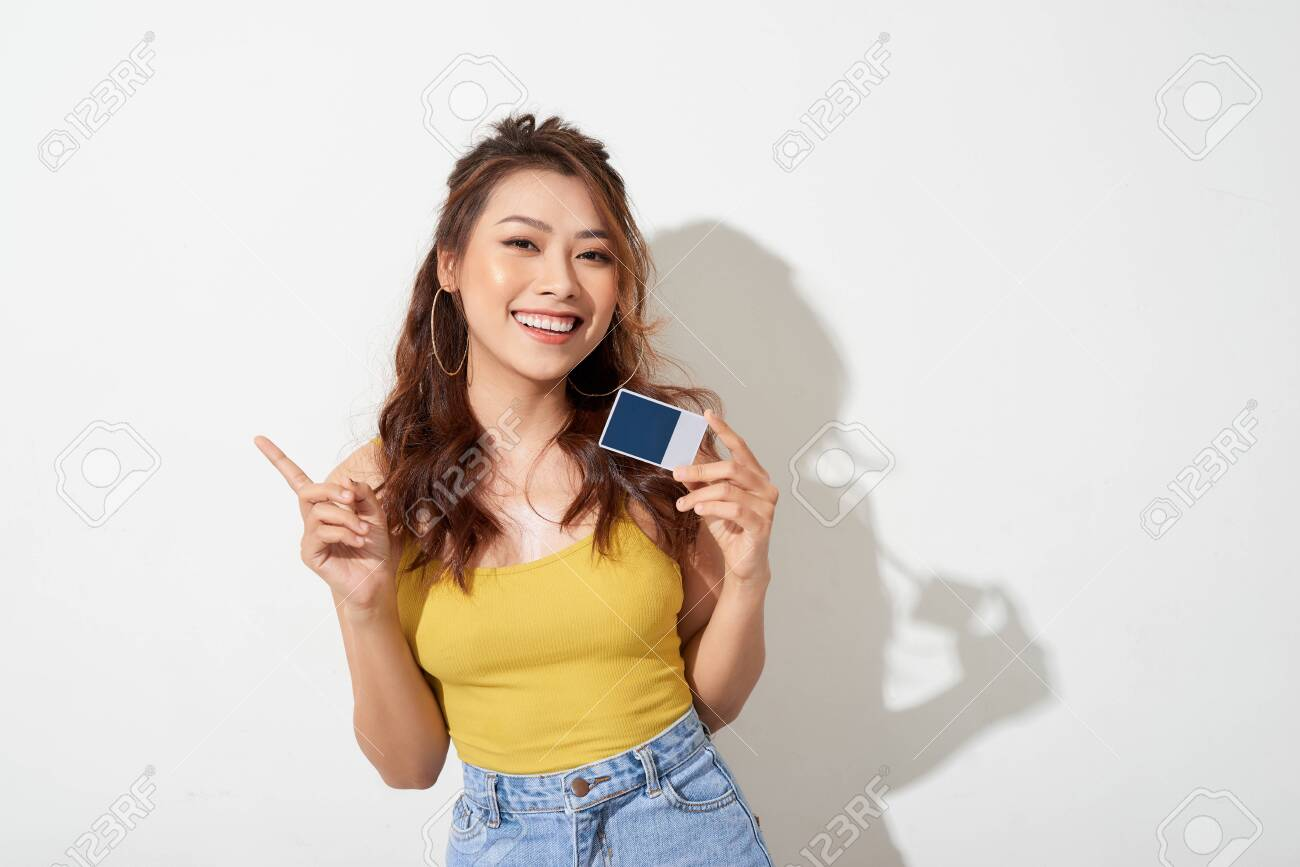 Photo of young smiling asian woman holding card - 129670597