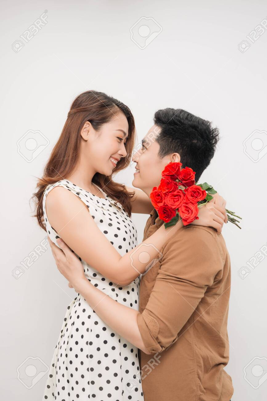 Portrait of cheerful lovely cute couple with beaming smiles hugging and looking to each other, - 132103353