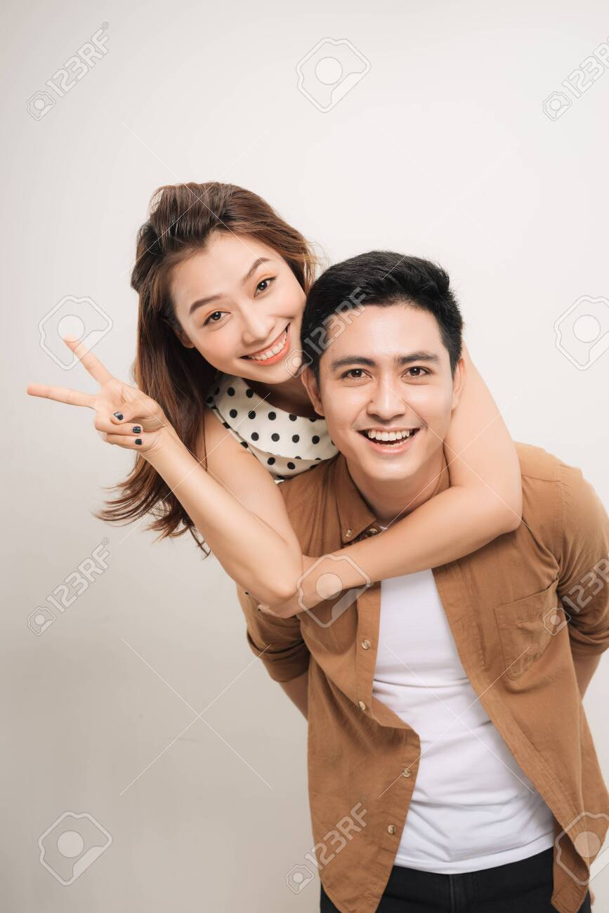 man carrying his lover on back, woman showing peace symbol over white background - 131919951