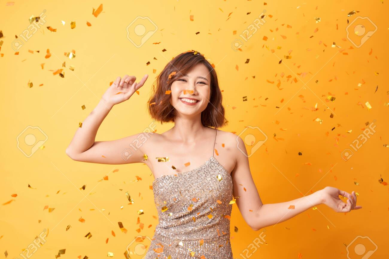 Young woman dancing under confetti at home, celebrating birthday - 133721141