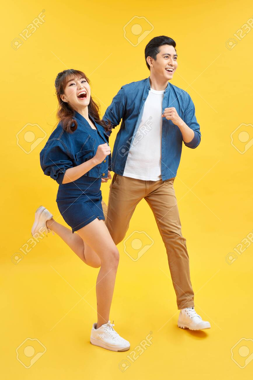 Attractive smiling young Asian couple being happy and amazed isolated on yellow studio background - 139673175