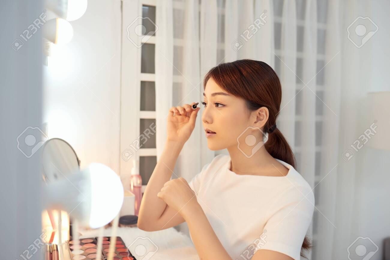 Young Asian woman applying mascara on her eyelashes - 138259393