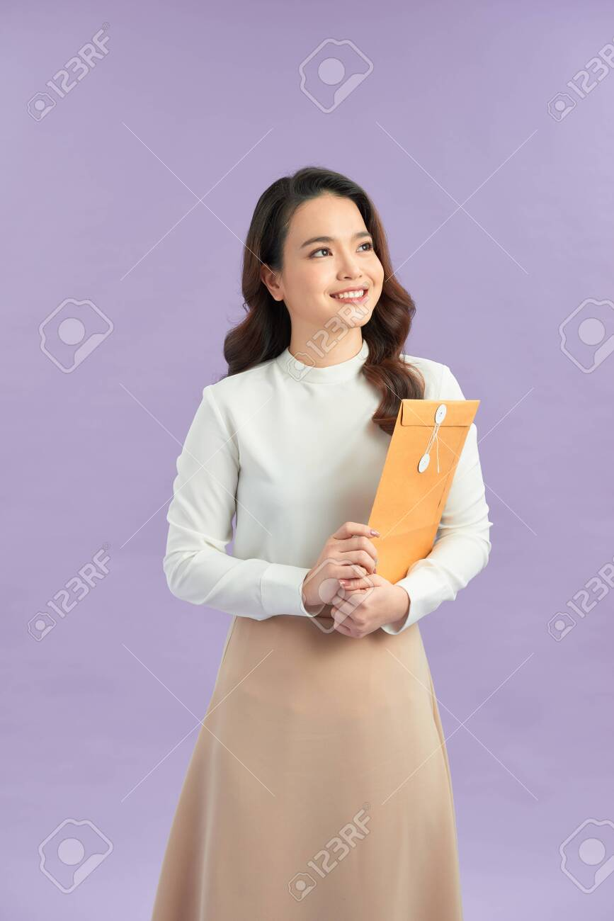 Woman hand holding brown envelope on purple background - 151558630