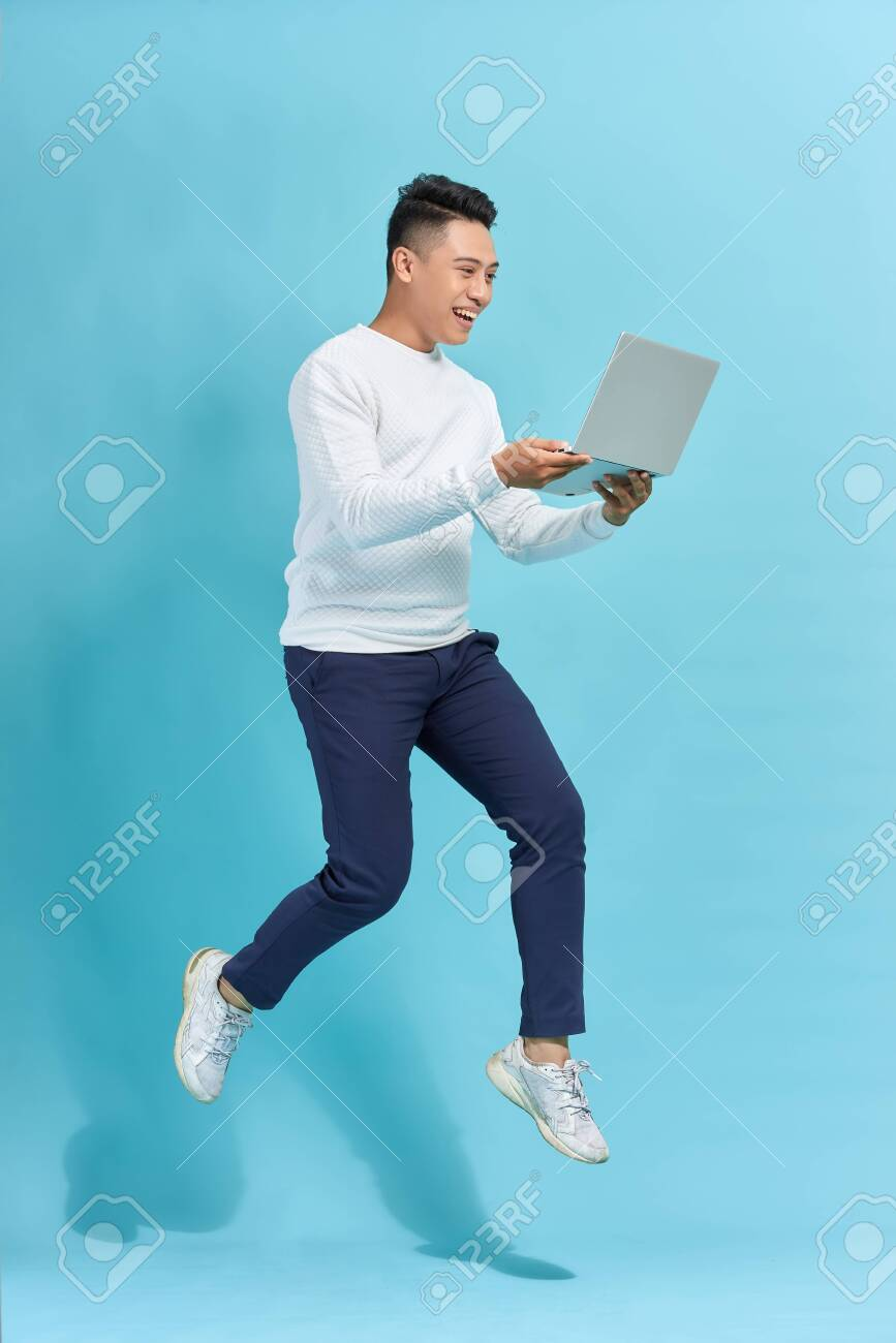 Full length portrait of happy man jumping and holding laptop isolated over blue background - 152717406