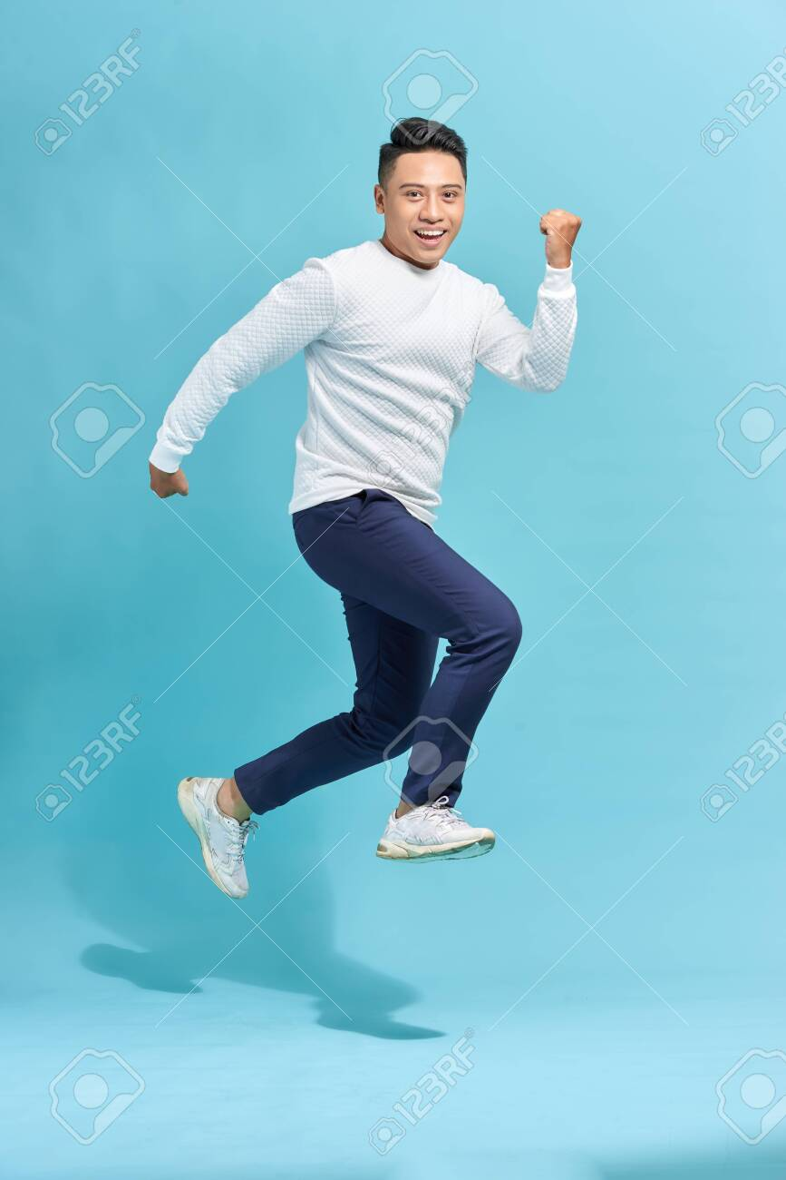 Image of cheerful young man dressed in black t-shirt jumping over blue background make winner gesture. - 153009464