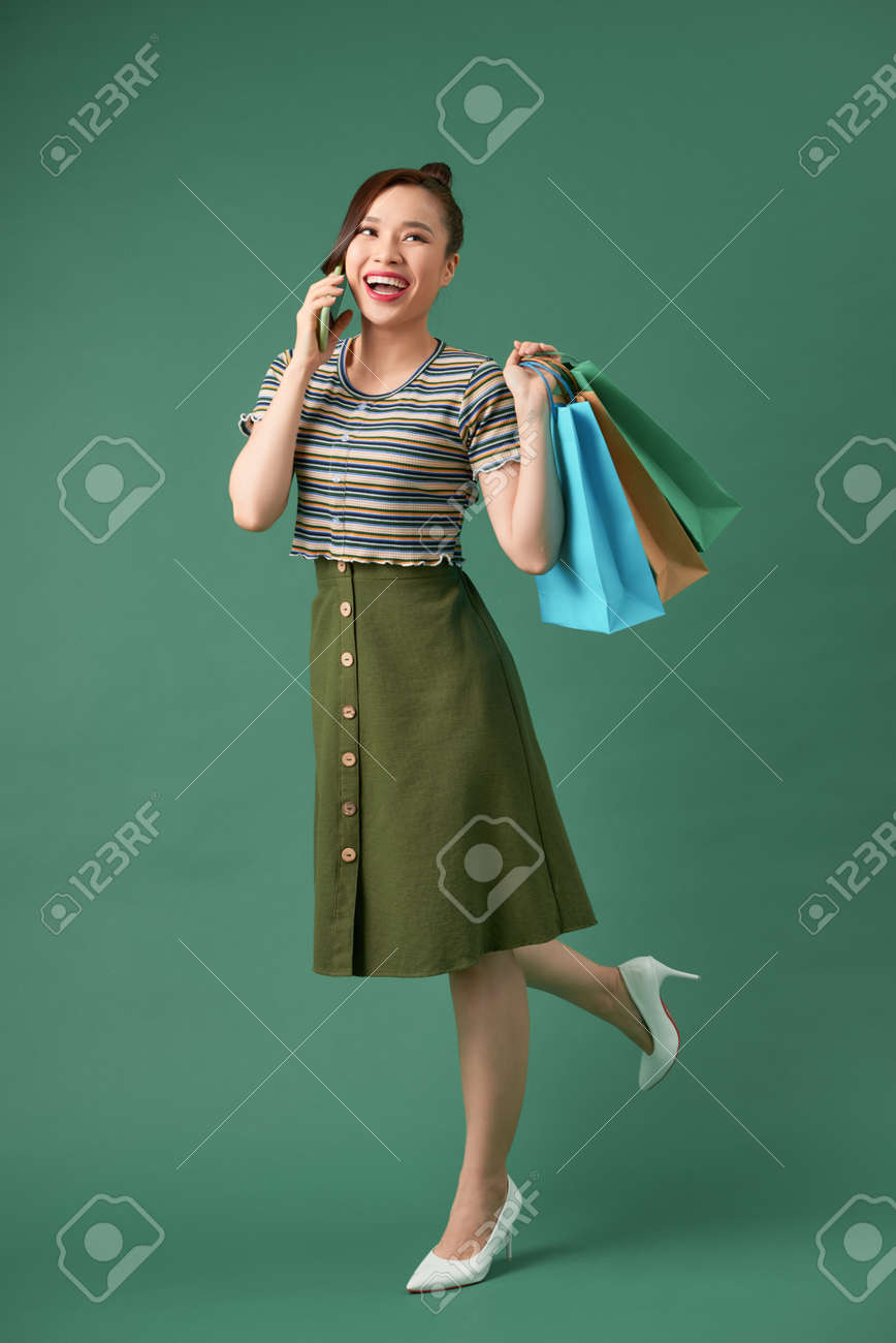 Portrait of happy young with shopping bags woman talking on cellphone - 155074648