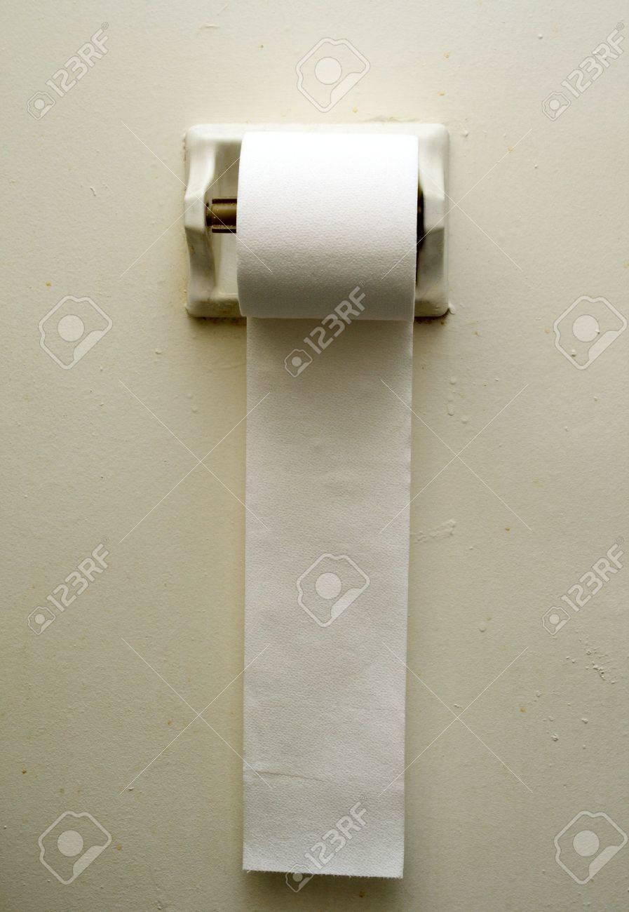 Hellgraue Wand toilettenpapier hängend gegen eine hellgraue wand lizenzfreie fotos