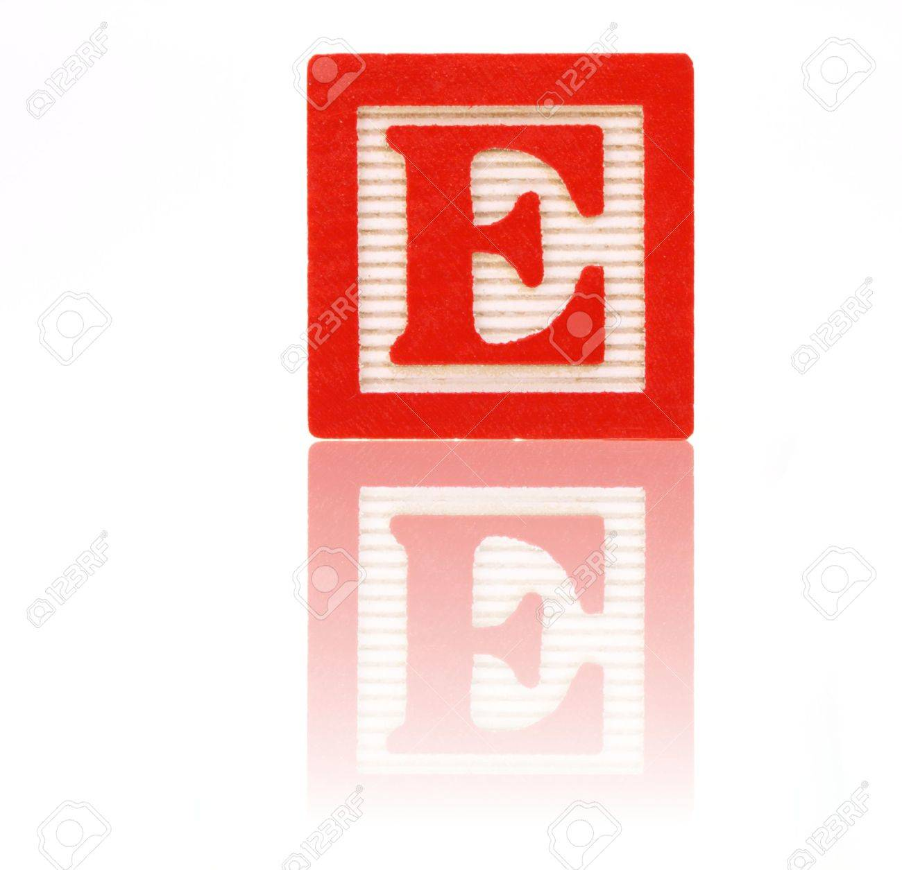 Letter E In An Alphabet Wood Block On A Reflective Surface Stock
