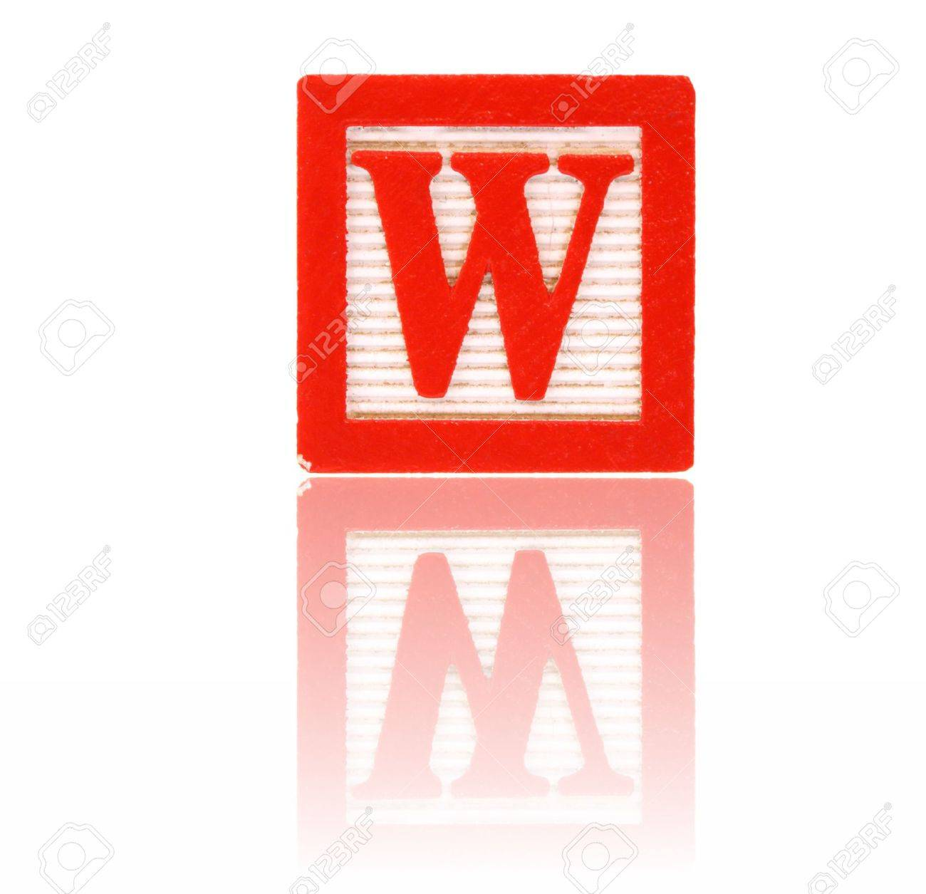 stock photo letter w in an alphabet wood block on a reflective surface
