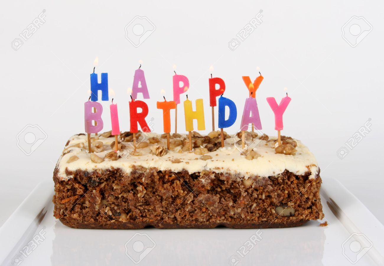 Birthday Cake Candles Lit On A Carrot Cake Stock Photo Picture And