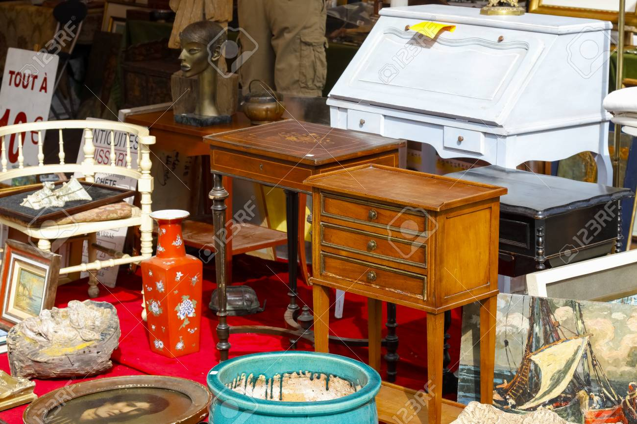 Nice, France - 17 September 2018: Second hand furniture and other interior furnishings are visible at the flea market in Cours Saleya, the famous city market offering antiques and many other products. - 117152676