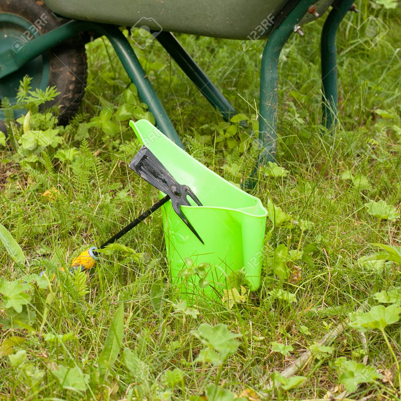 Stock Photo   Tools For Gardening. Rake, Watering Can And Wheelbarrow On  Grass