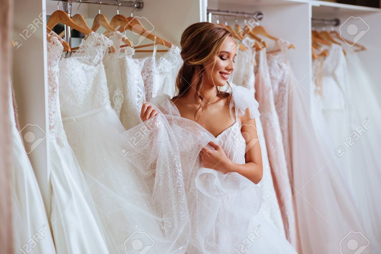 Beautiful bride is trying on an elegant wedding dress - 110131256