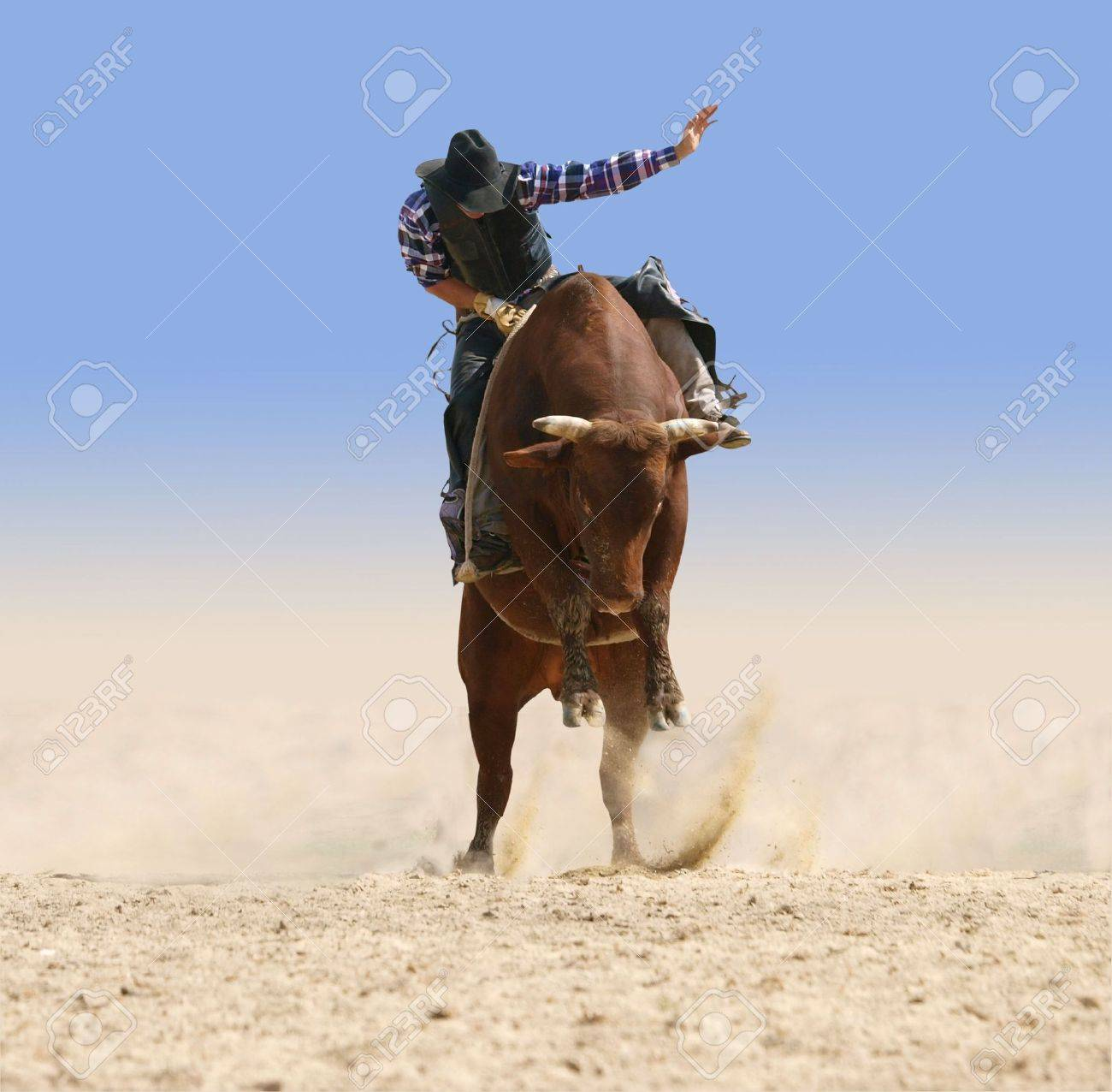 Cowboy Riding a Large Red Bull - 6176845