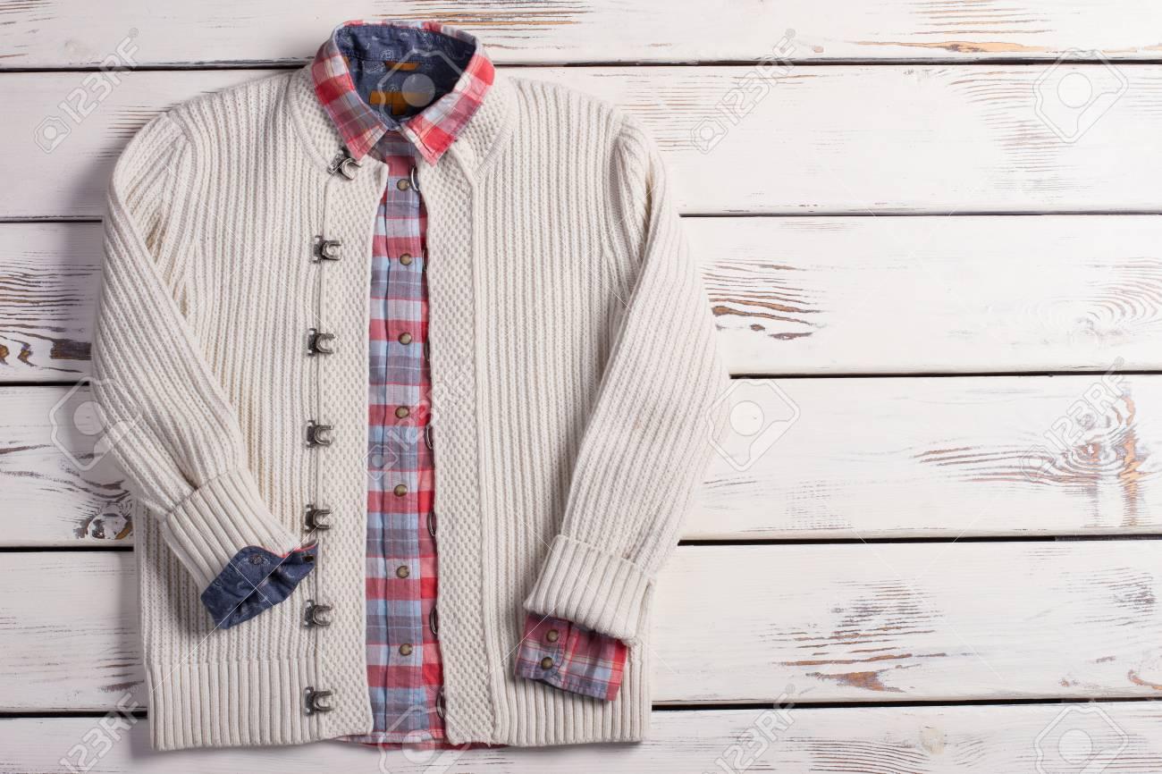 Suéter de punto blanco con una camisa a cuadros sobre un fondo de madera. Estilo de los hombres de ropa de invierno.