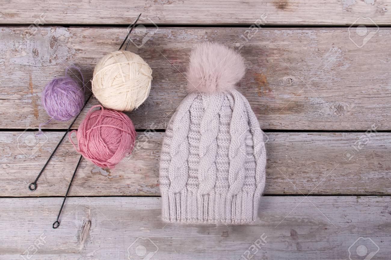 b6f182c4948 Light gray handmade knitted hat on retro boards. Beautiful yarn with  knitting needles. Handmade