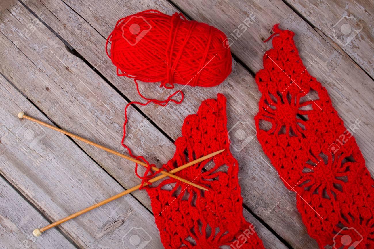 9cefd3efde35 Banque d images - Fabrication d écharpe rouge. Fil de laine rouge vif et  aiguilles en bois sur fond rustique. Tricot et crochet blog.