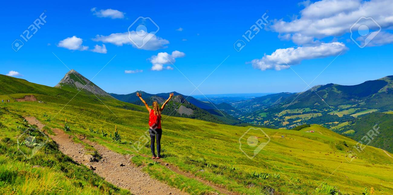back view of backpacker tourist girl on the mountain in France, Cantal - 151881414