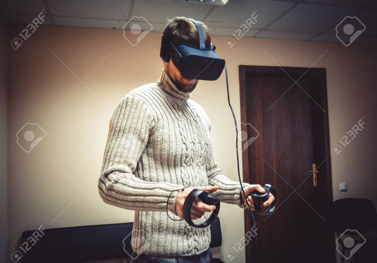 9fa80a6d696 Man in helmet virtual reality plays game. Man uses VR-headset display with  headphones