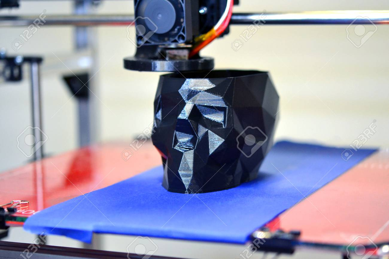 3D printer printing a model in the form of black skull close-up. The 4ht industrial revolution. Automatic three dimensional performs plastic modeling. Progressive modern additive technology - 97216248