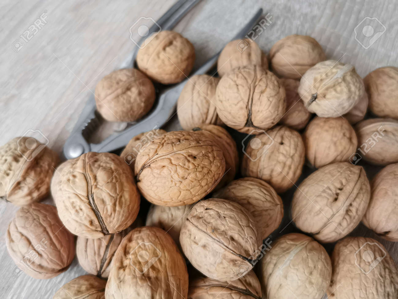 Whole walnuts and nutcracker on a wooden table - 160739272