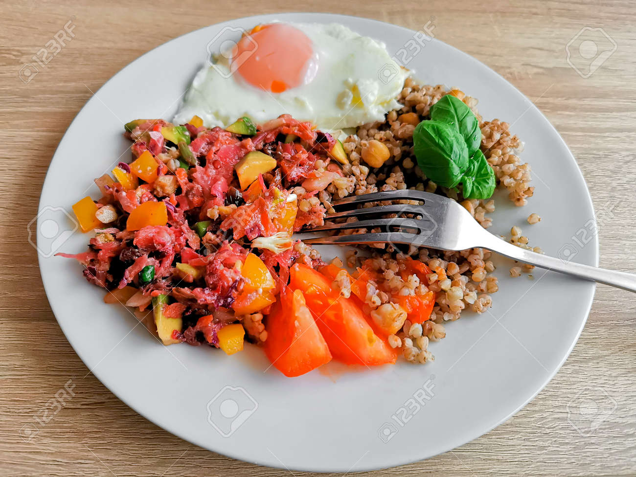Buckwheat groats with chickpeas, basil leaves, soft-boiled egg and vegetable salad. A healthy and nutritious meal - 160902131