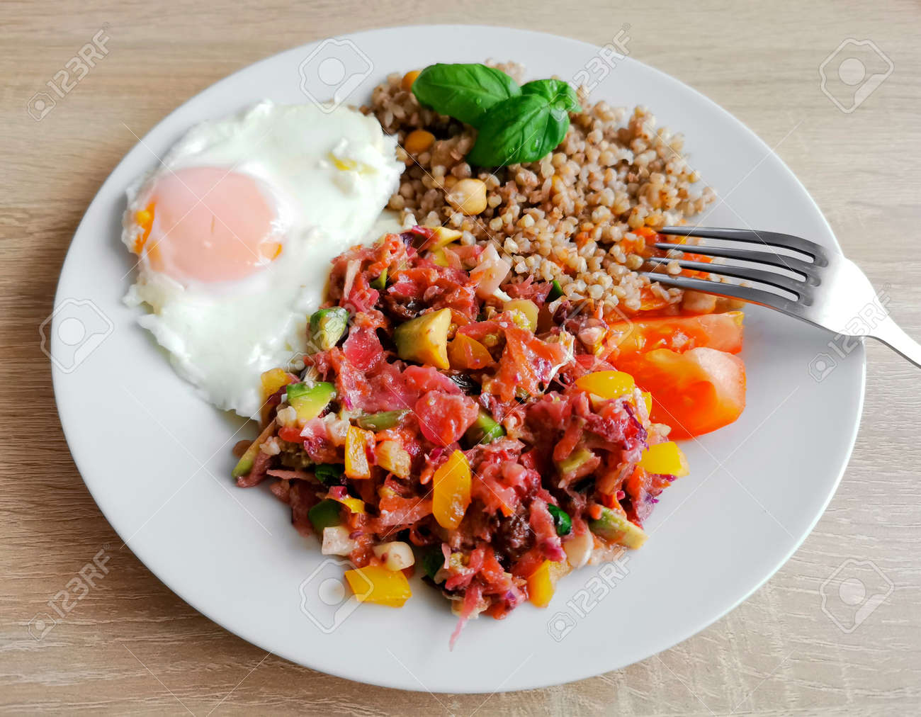 Buckwheat groats with chickpeas, basil leaves, soft-boiled egg and vegetable salad. A healthy and nutritious meal - 160902132