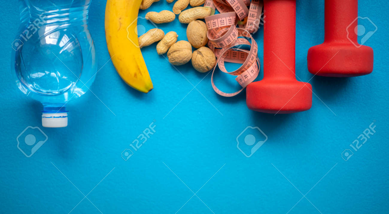Banana, nuts, water, measuring tape and dumbbells on a blue background. Food and fitness equipment for a healthy lifestyle - 160956034