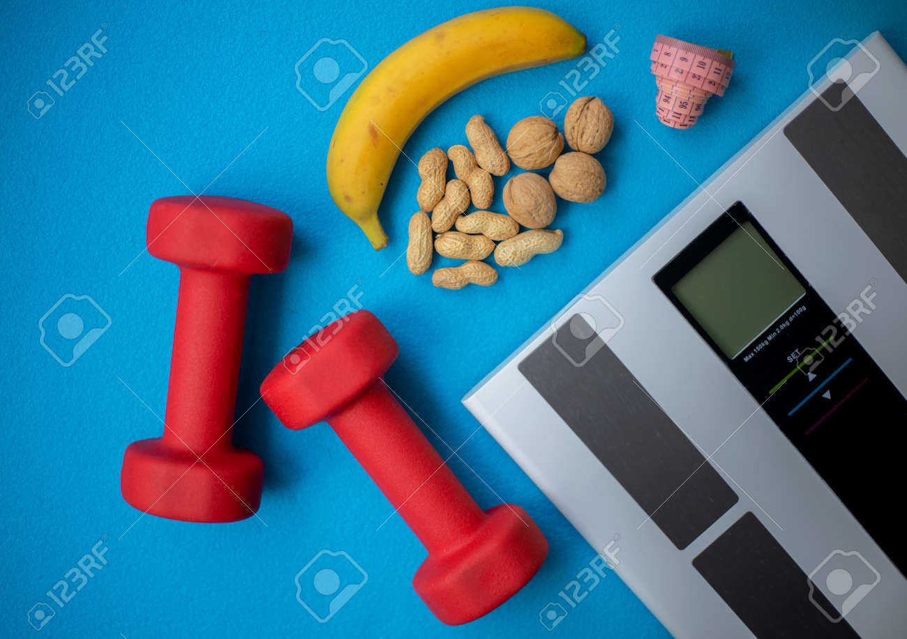 Electronic scale, banana, nuts, measuring tape and dumbbells on a blue background. Food and fitness equipment for a healthy lifestyle. Keep your body in good shape - 161019319