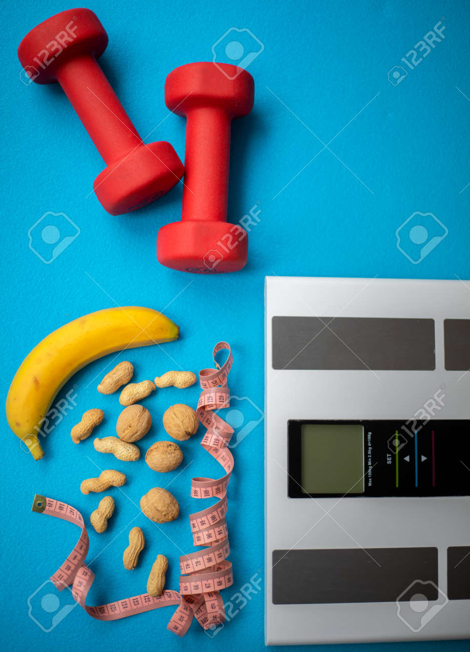 Electronic scale, banana, nuts, measuring tape and dumbbells on a blue background. Food and fitness equipment for a healthy lifestyle. Keep your body in good shape - 161019323