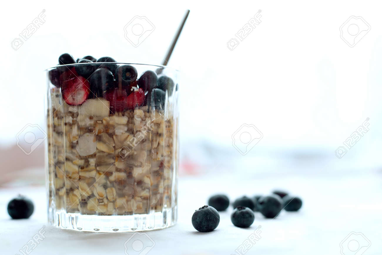 Breakfast, food, healthy eating and diet concept - close glass of granola oatmeal with chia, cranberry and american blueberries on table - 161313158