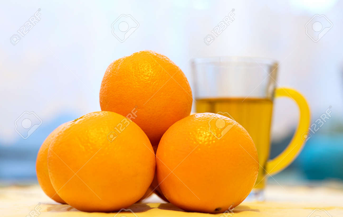 A cup of orange tea and fresh, ripe, juicy oranges on the table - 161313164