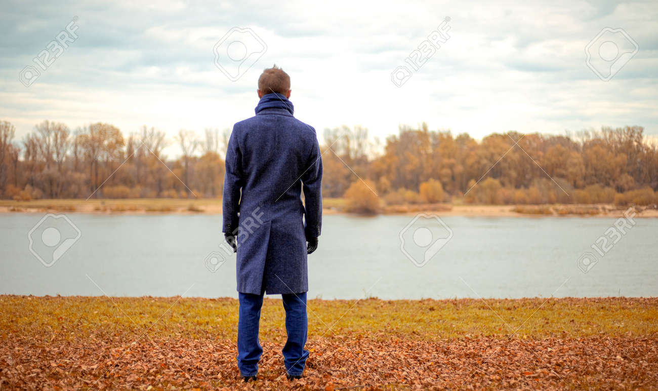 A man stands on the bank of a river on a cold autumn day - 161685725