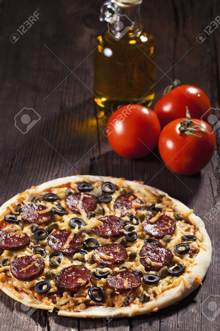 Sliced tasty salami pizza on rustic background Stock Photo - 18151070