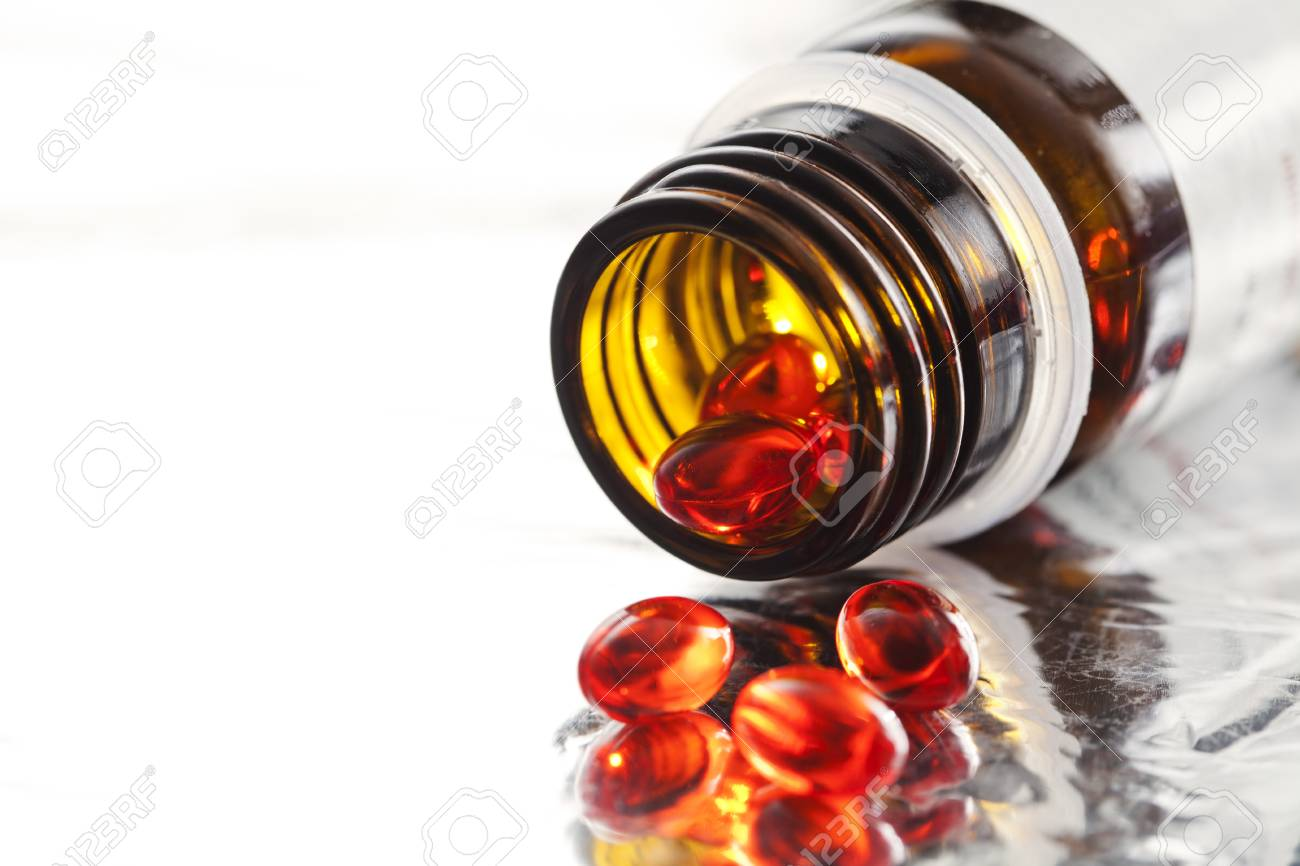 Orange vitamin pills and pill bottle Stock Photo - 19009156