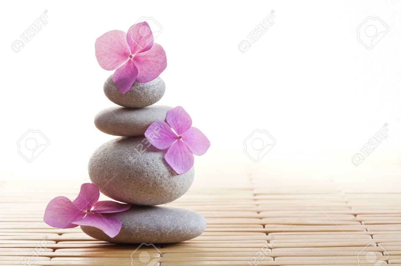 Archivio Fotografico , Pila di pietre zen e fiori rosa sulla stuoia di bambù