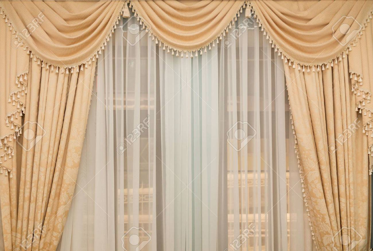 classic beige curtain hanging on a window Stock Photo - 24600327