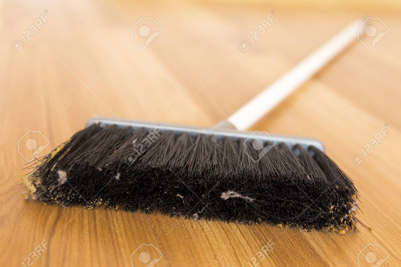 sweeping dust with black broom on a wooden floor stock photo