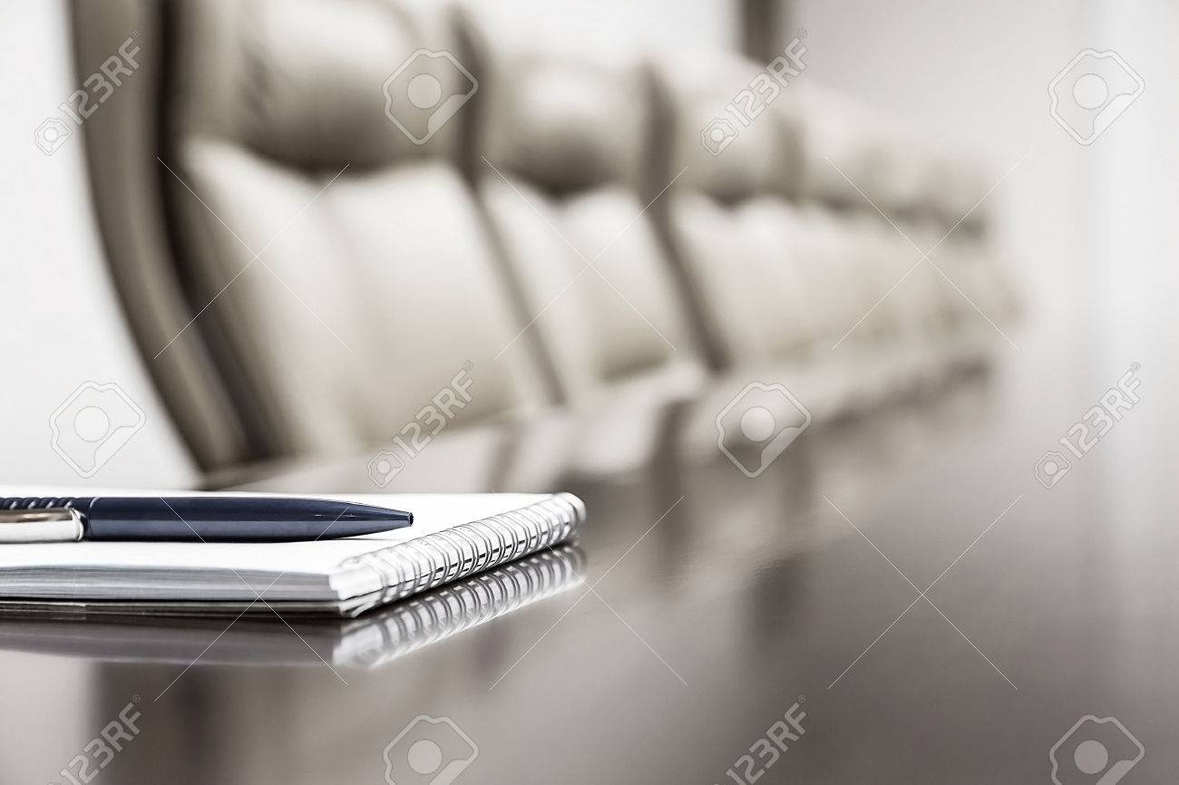 Closeup of notepad kept on table in empty conference room - 33545475