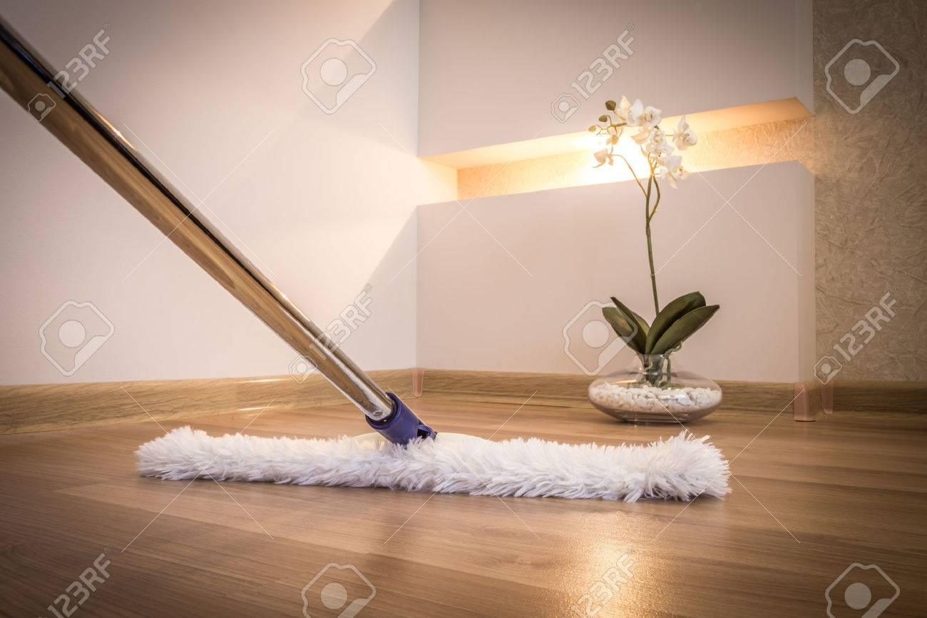 Modern white mop cleaning wooden floor in house - 43025255