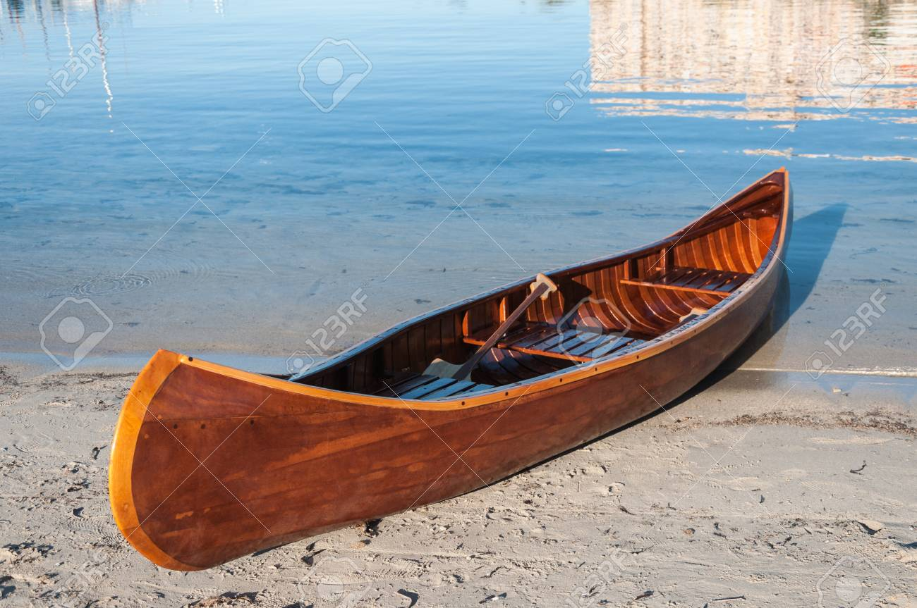 Wooden Canoe On The Sand With Sea In Background Stock Photo