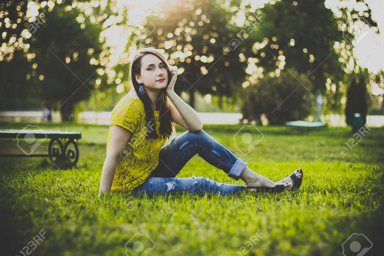 Young beautiful woman in yellow blouse and blue jeans sitting in a park on the grass holding head on hand and smiles in the warm summer evening. Photo of a girl with back sunlight on the nature. - 166281031