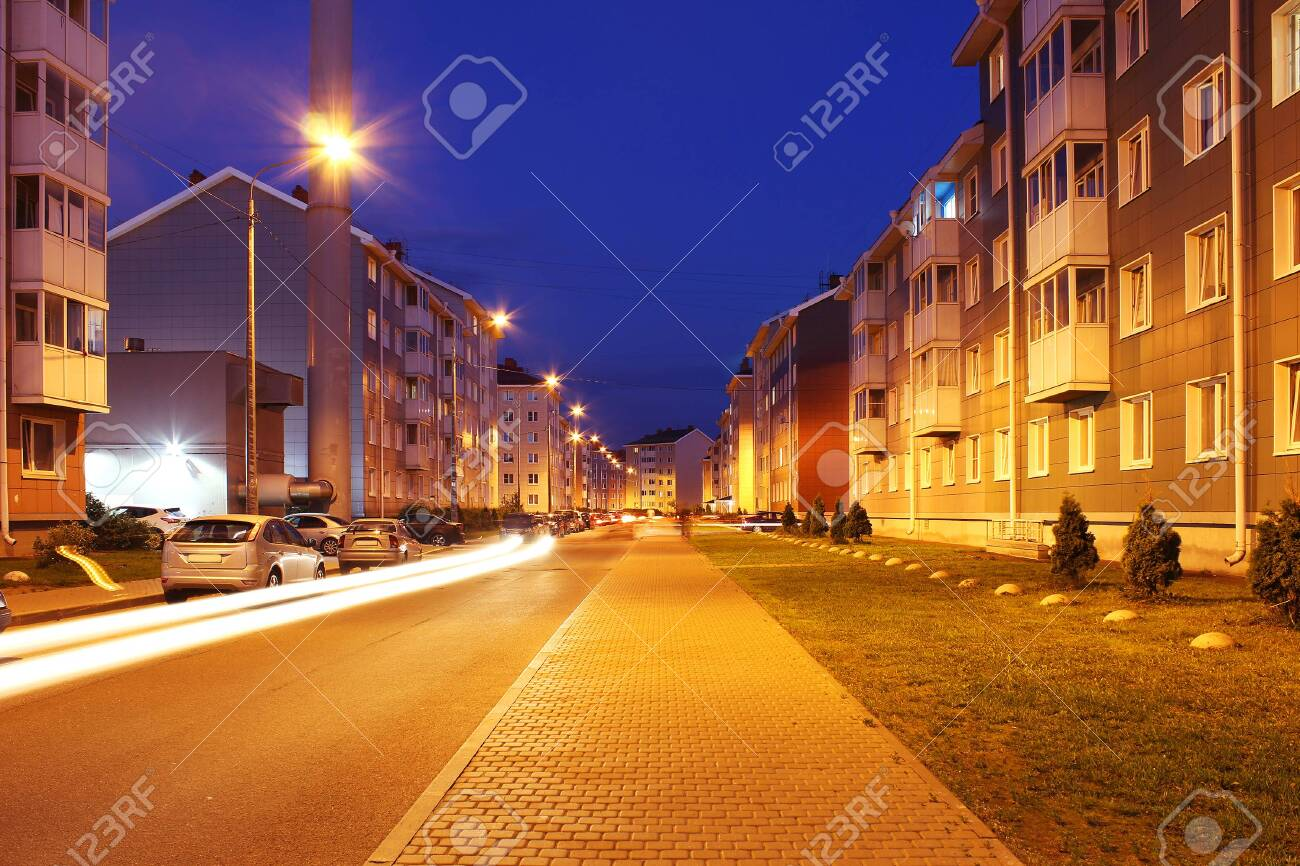 Empty street of town lit by street lights at night. - 137243786