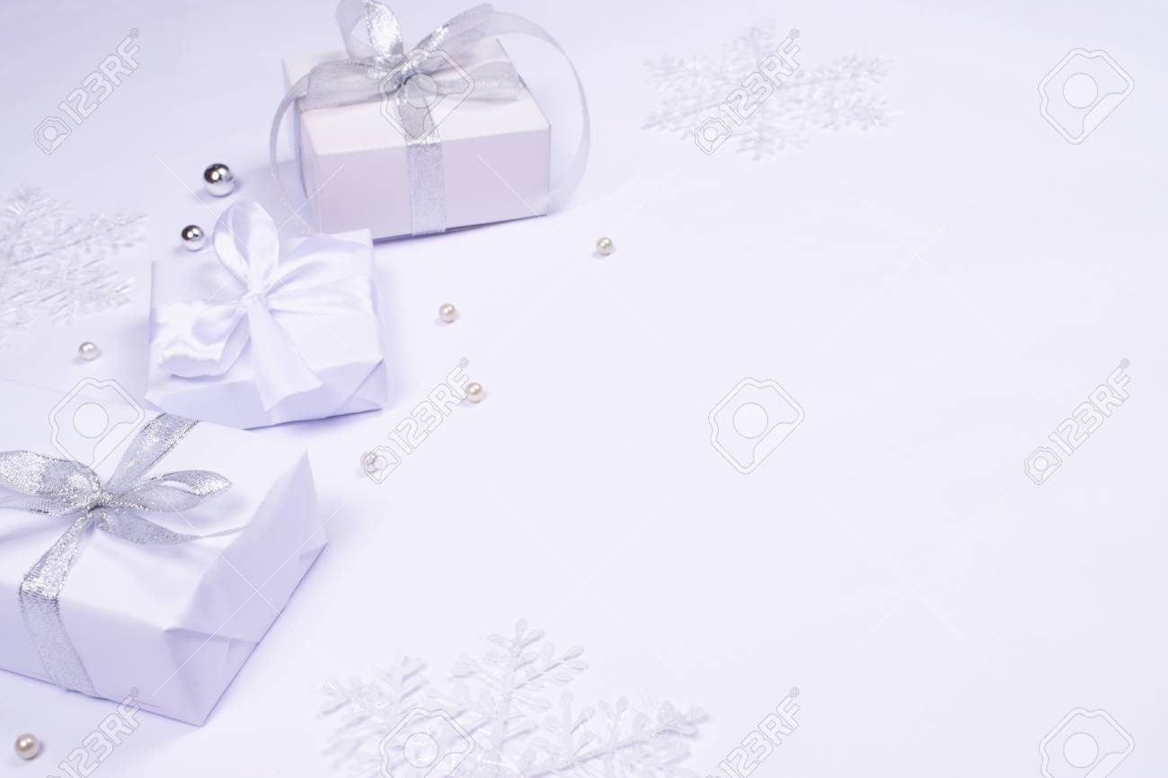 Three Elegant White Gift Boxes Tied Up With Silver And Silk Ribbons