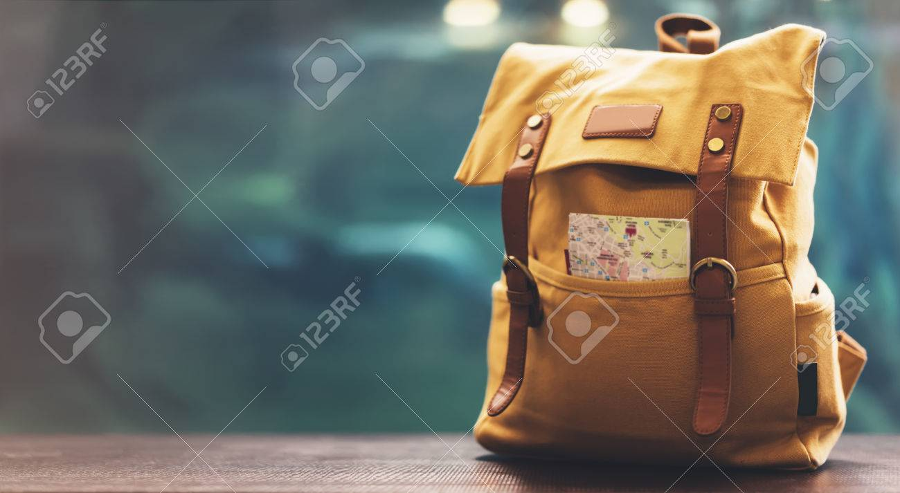 Hipster yellow backpack and map closeup. View from front tourist traveler bag on background blue sea aquarium. Person hiker visiting oceanarium museum in Barcelona on backdrop, blank blurred mockup - 72754670